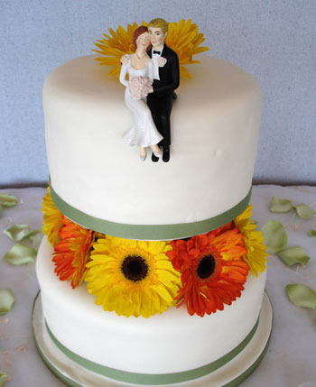 Couple sittign on wedding cake, whimsical cake topper