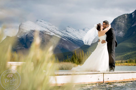 couple kissing by glacial lake in the Rockies