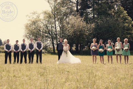 The bridal party, happily posing in a field