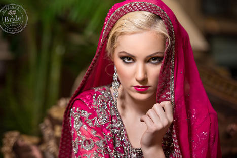 bride gazing into camera wearing a dupatta draped head and red and silver lehenga