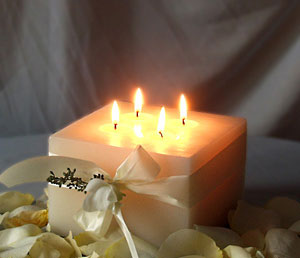 A Large square white candle as a winter wedding centrepiece
