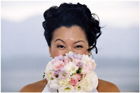 Happy bride with fresh flower bouquet. Photo by Hamid Attie, Vancouver